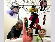 Sewing instructor Debbie Sementelli encourages Seleana as she hangs her fashionable crow; Heavenly awaits her turn to populate the class's tree.