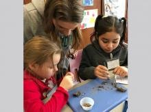 With guidance from a college student volunteer, the children examined the contents of an owl pellet.