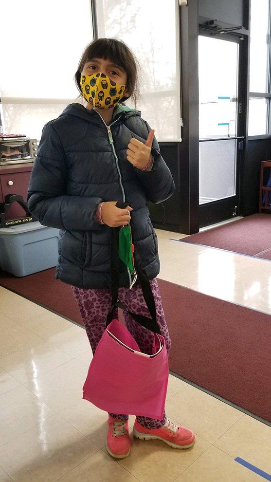 A student picking up her art supplies.